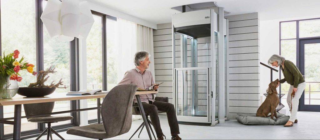 Pareja de la tercera edad disfrutando en su hogar al lado de un ascensor unifamiliar instalado en el interior de la casa